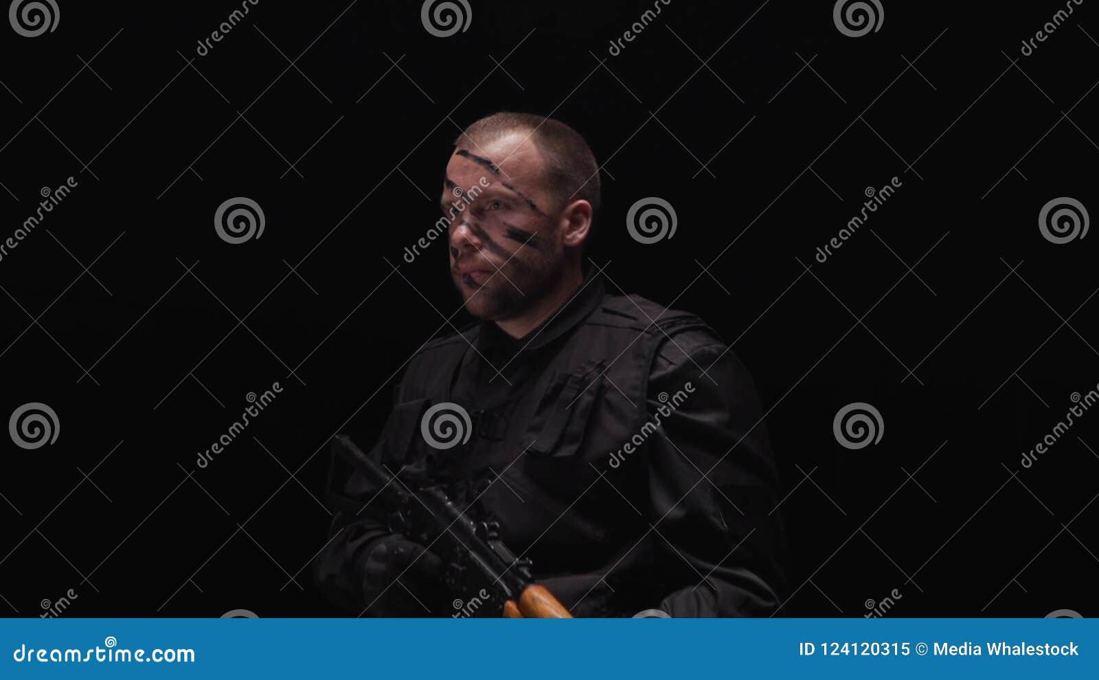 穿军服的英俊的战士画象,被绘他的在黑背景的面孔 股票 人军人赞许