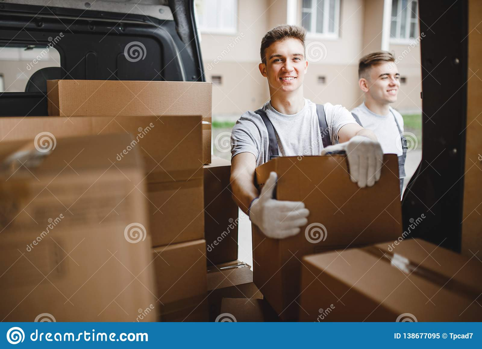 穿制服的两名年轻英俊的工作者在搬运车箱子旁边充分站立 议院移动,搬家工人服务