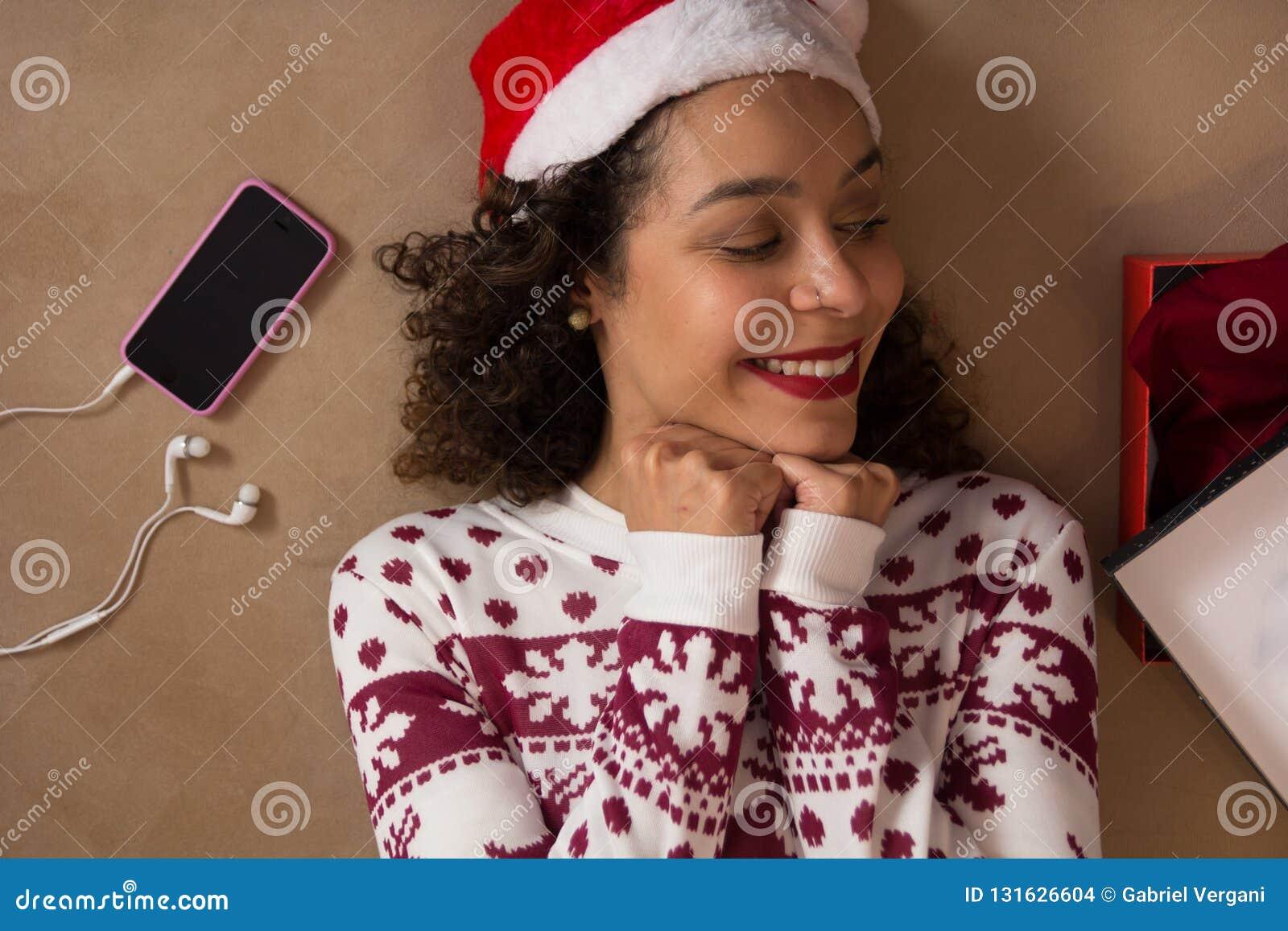 穿圣诞老人帽子和圣诞节毛线衣的非裔美国人的妇女躺下和看礼物盒