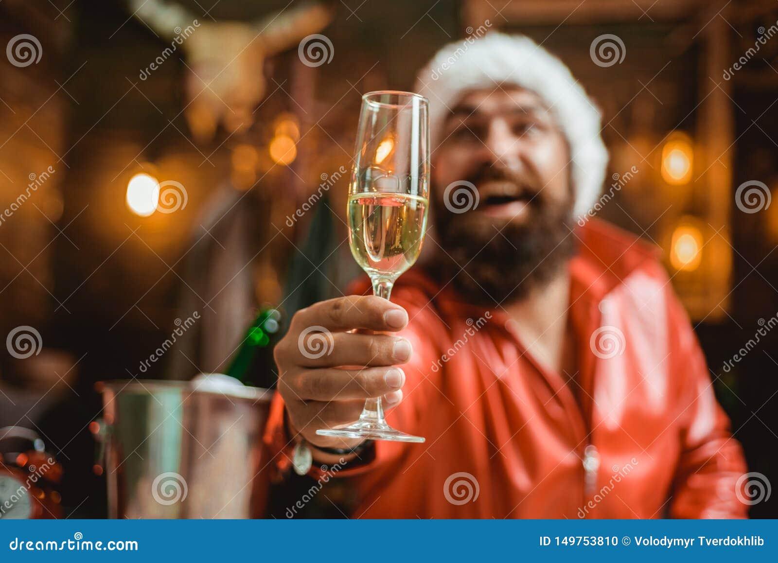 穿圣诞老人衣裳的英俊的强壮男子的人 有胡子的人拿着杯香槟 ??
