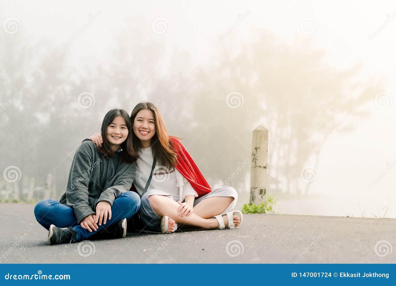 穿在旅游景点的两亚裔女孩亲密朋友一件毛线衣沿在水库旁边的路在大雾