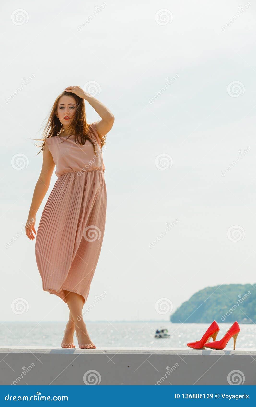 穿在跳船的妇女长的浅粉红色的礼服