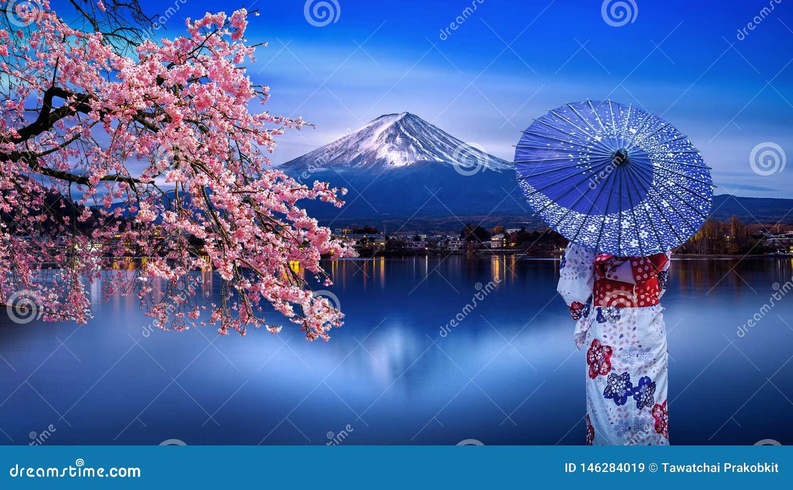 穿日本传统和服的亚裔妇女在富士山和樱花,Kawaguchiko湖在日本