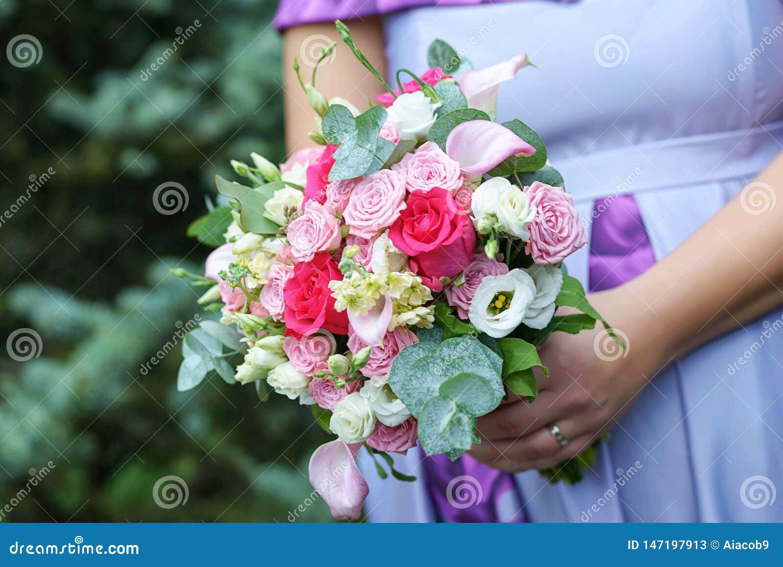 穿显示可爱宝宝爆沸和拿着婚姻的花束的一件淡紫色夏天礼服的白种人女性客人或女傧相