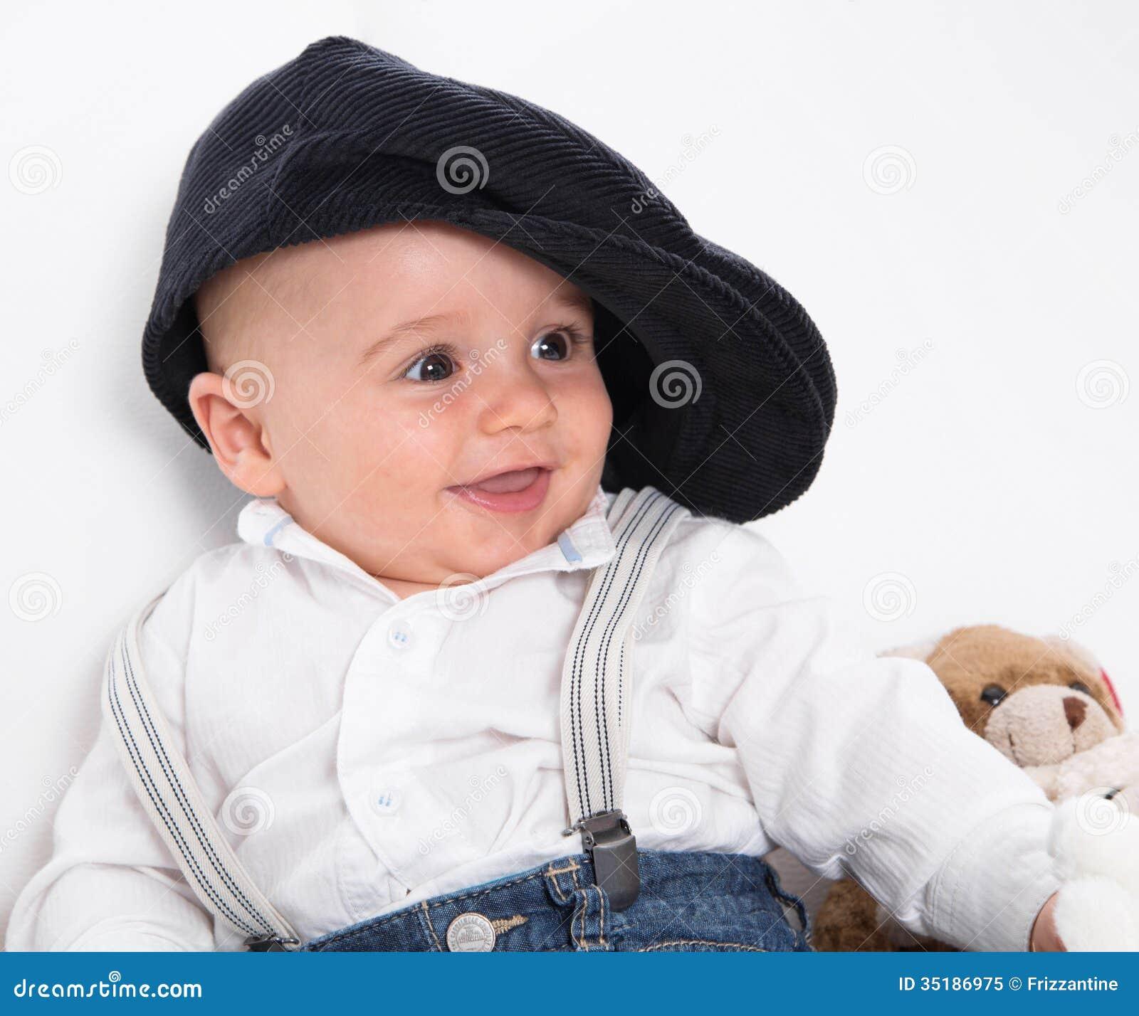 穿法国贝雷帽的笑的婴孩和蓝色牛仔裤
