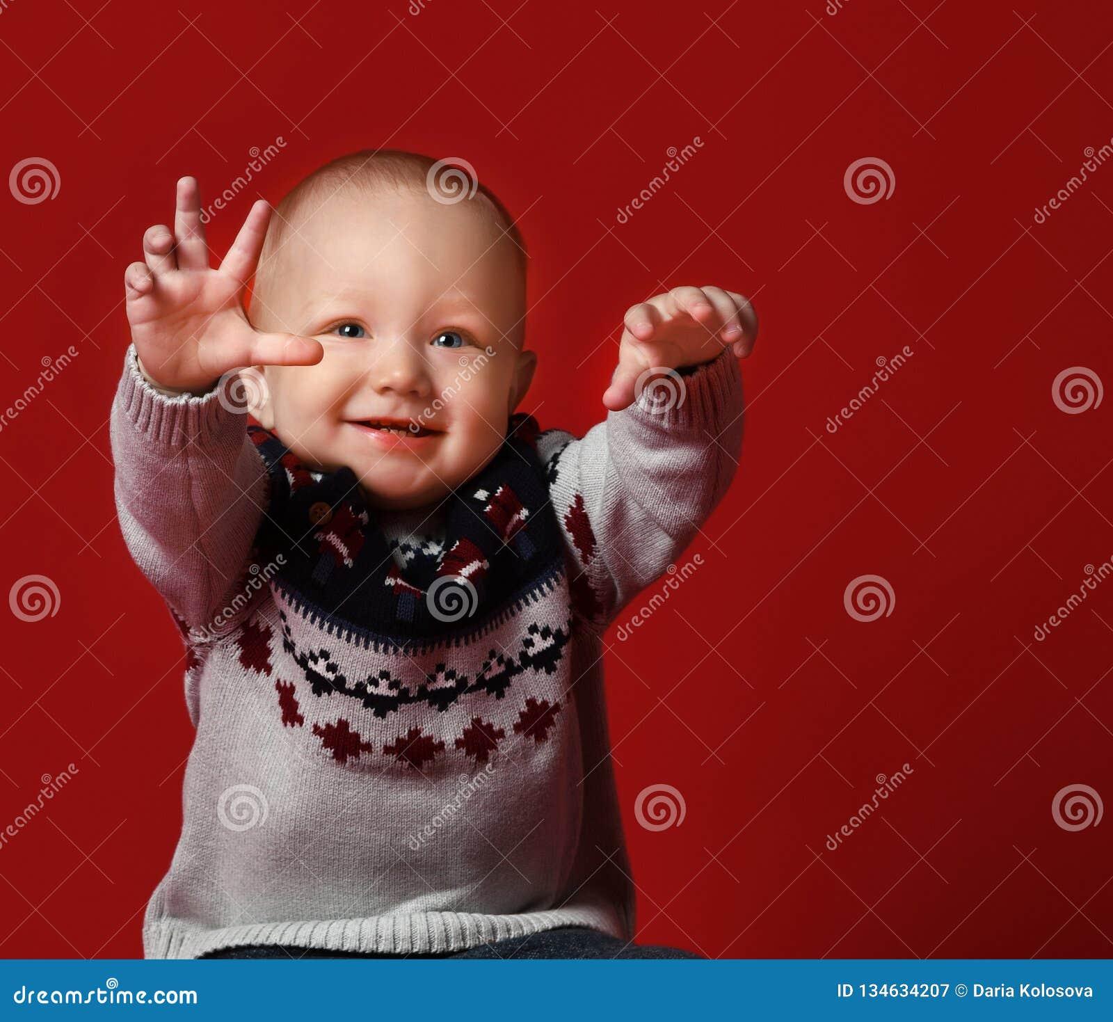 穿温暖的被编织的圣诞节毛线衣的滑稽的矮小的婴孩在演播室在寒冷冬天天