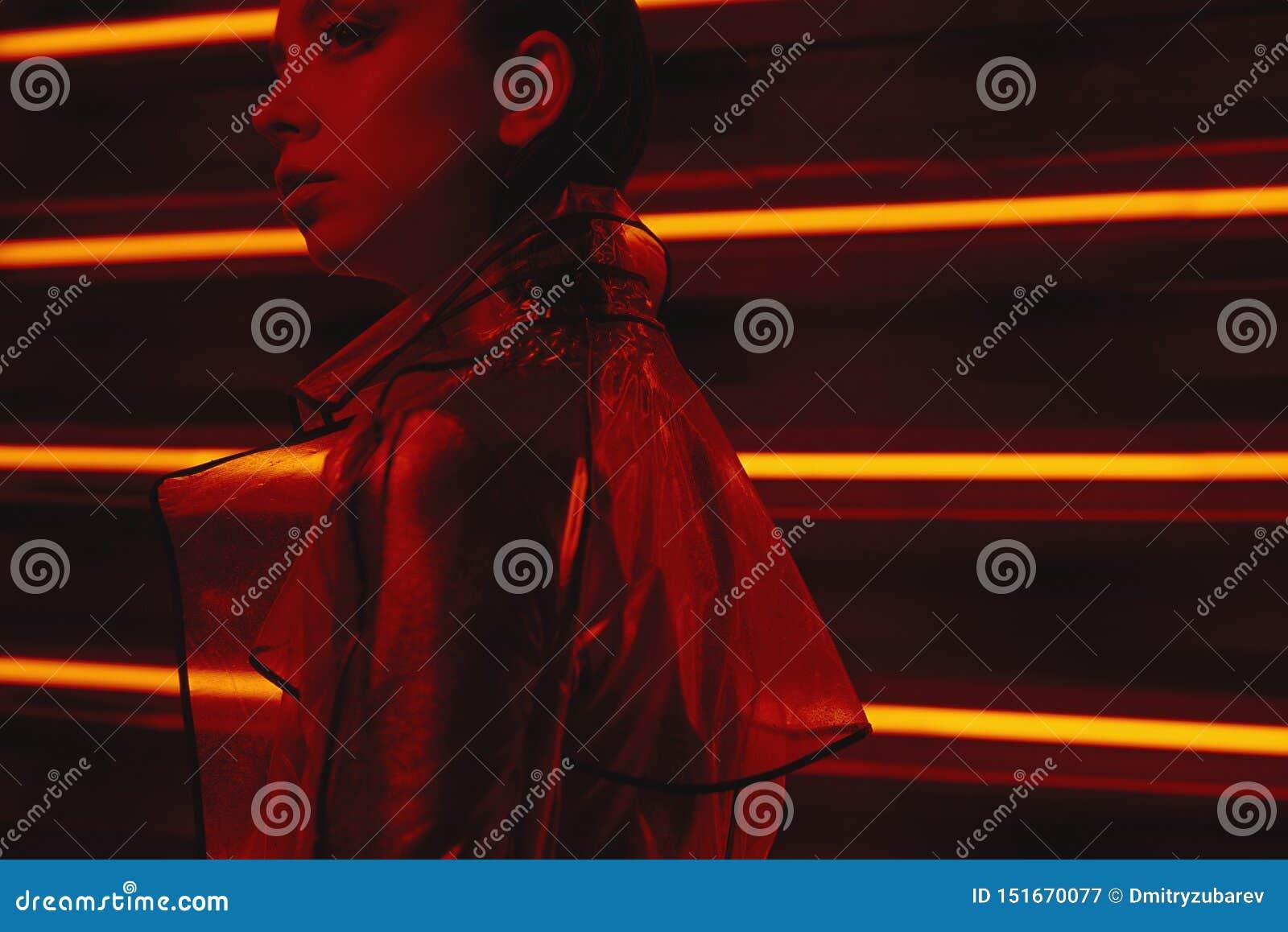 穿玻璃纸和红色礼服的透明外套模型计算机国际庞克射击对氖墙壁