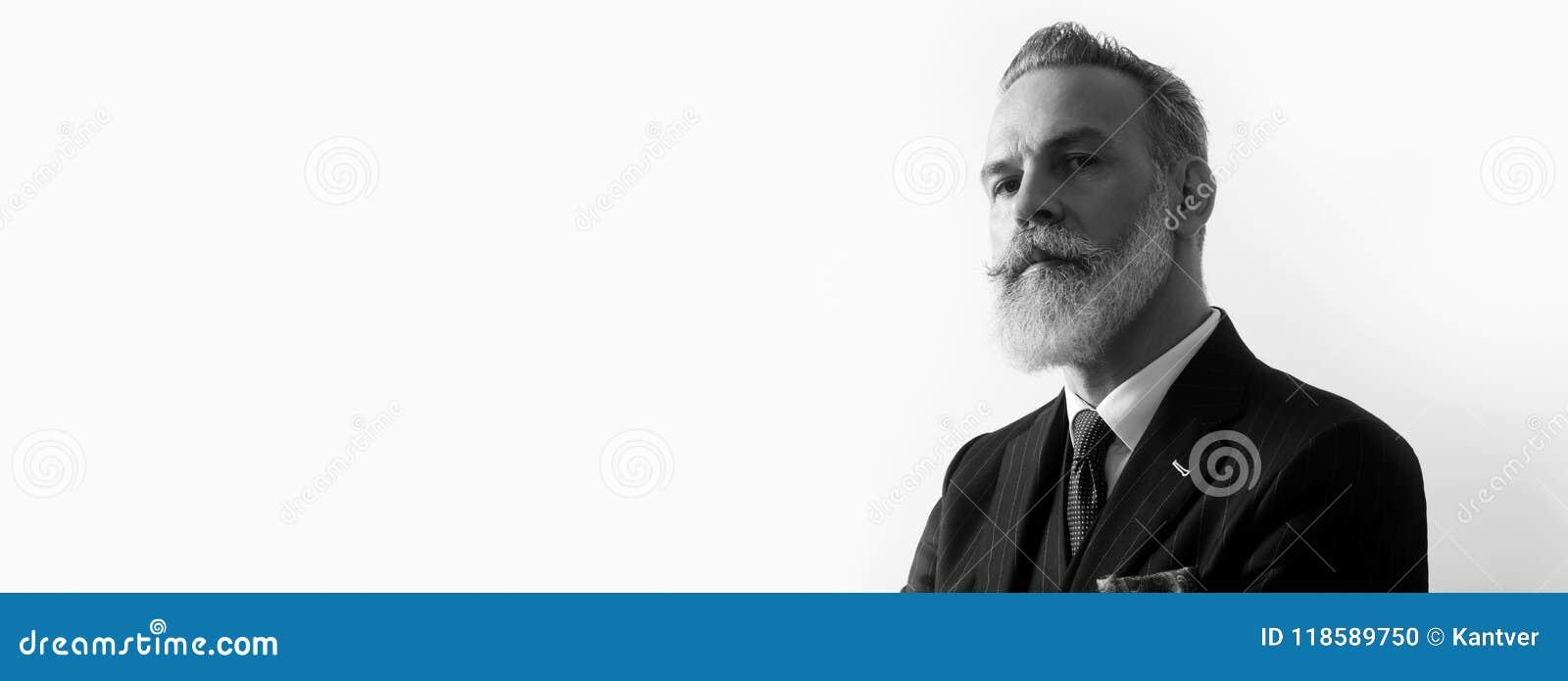 穿着在空的白色背景的有胡子的英俊的绅士画象时髦衣服 复制浆糊文本空间 宽