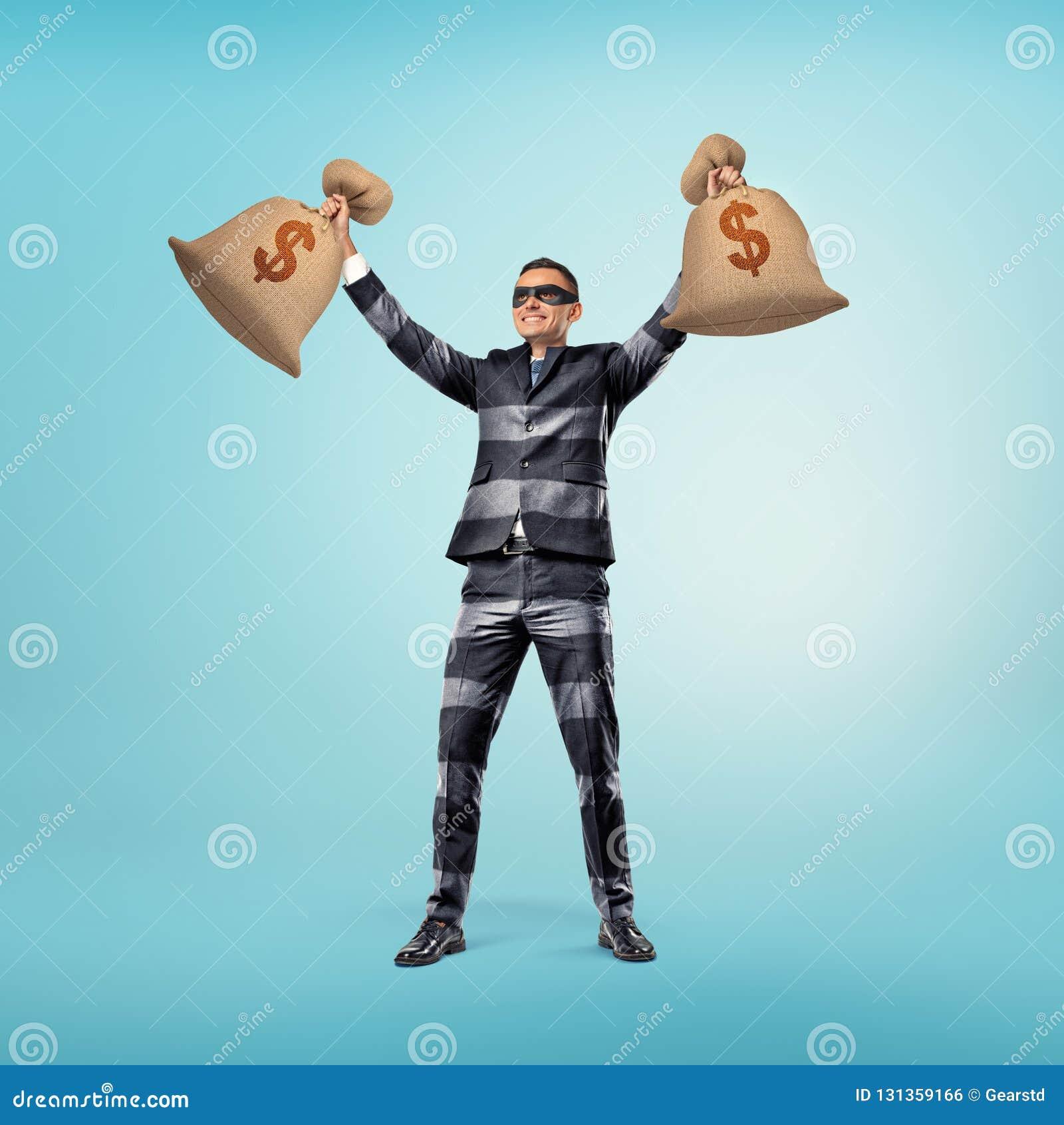 穿着类似夜贼的成套装备和黑眼圈眼罩有条纹的商人的经典衣服站立与他的