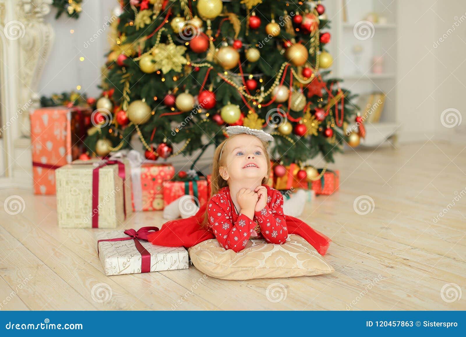 穿红色礼服的小女孩说谎在圣诞树和礼物附近
