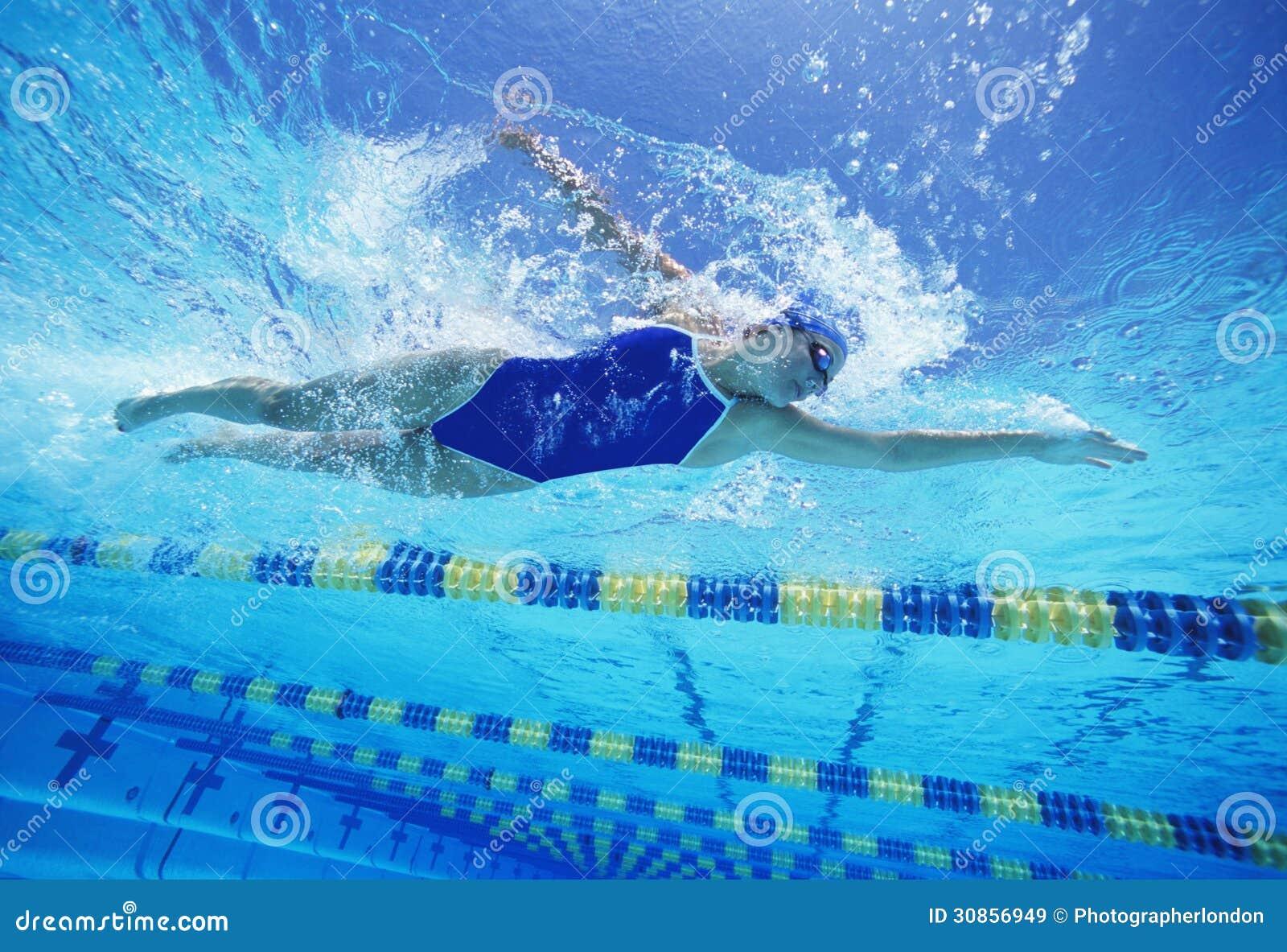 穿美国泳装的女性游泳者,当游泳在水池时
