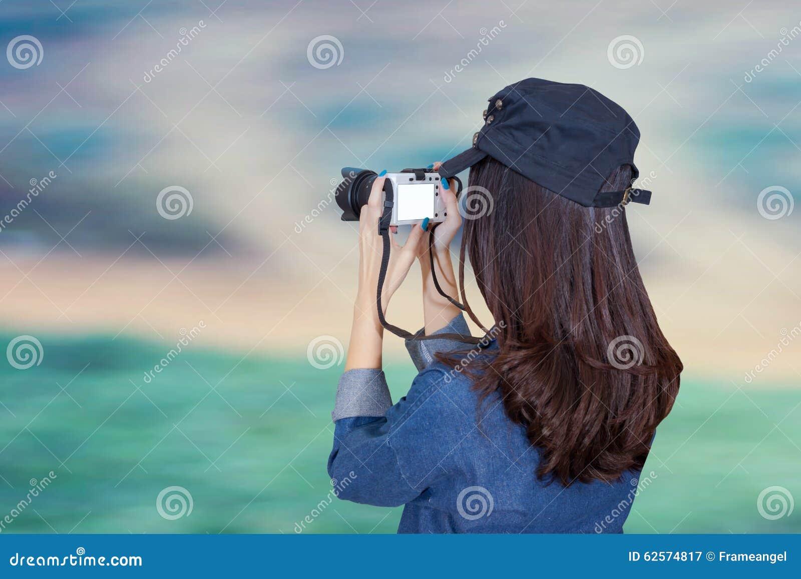 穿蓝色礼服的妇女旅客作为摄影师,采取照片wi