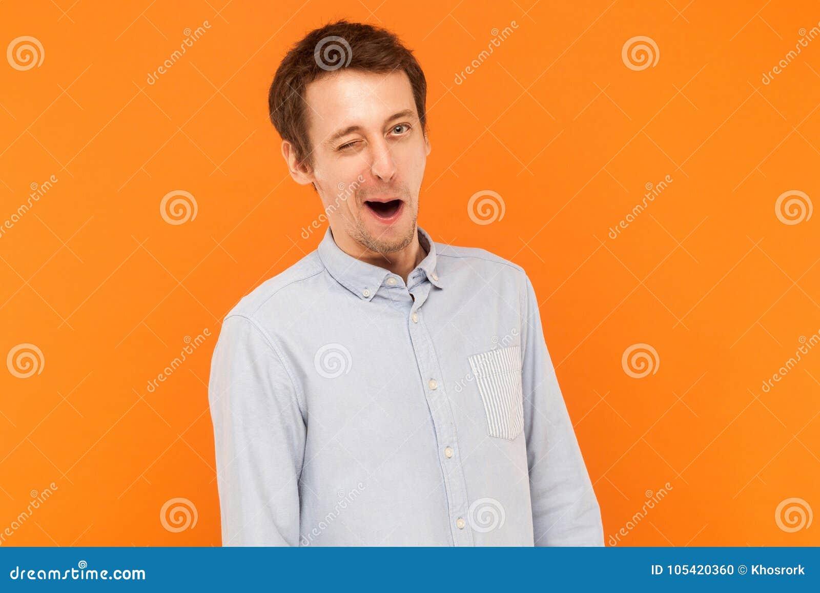 穿蓝色衬衣,在照相机的闪光的情感商人