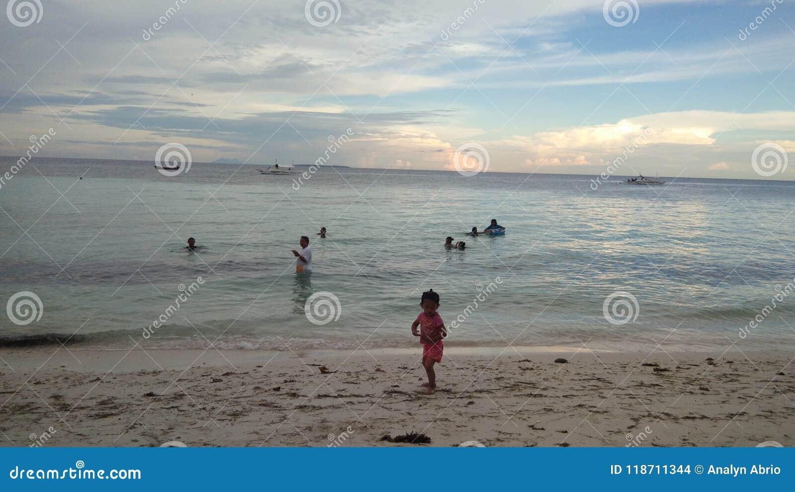 穿蓝衣的男孩服务台女孩查找海运坐的冲浪