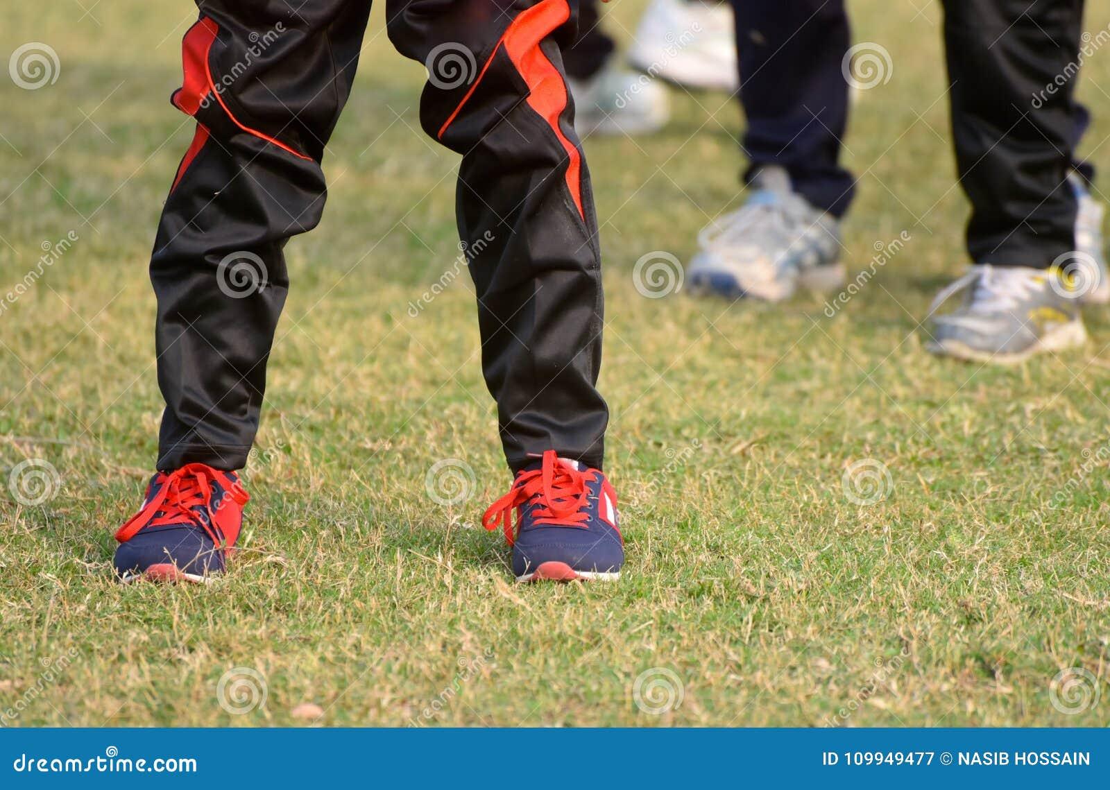 穿长裤&鞋子的玩板球者腿库存照片