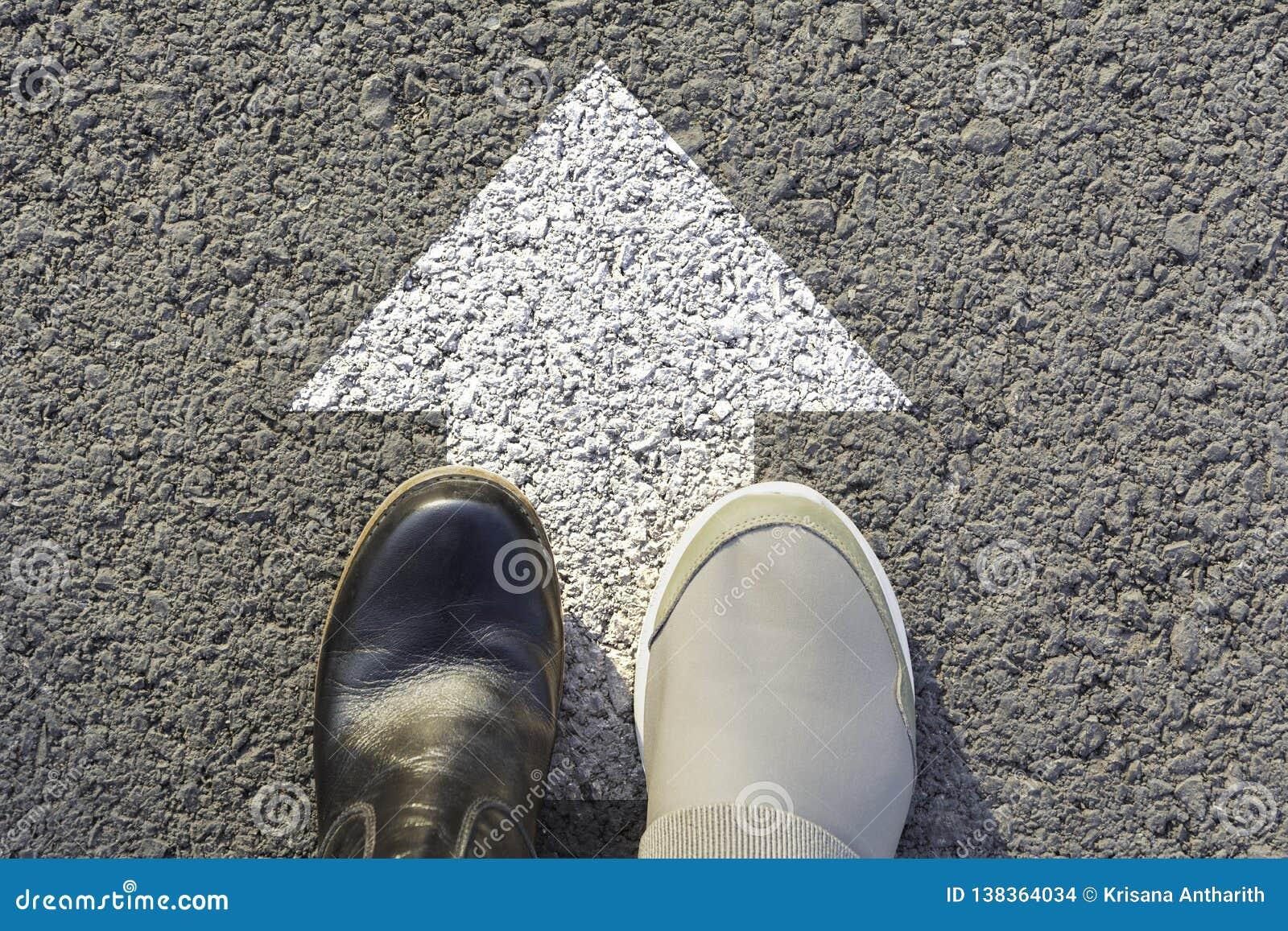 穿黑白鞋子的人顶视图选择方式标记用白色箭头 选择正确的道路概念