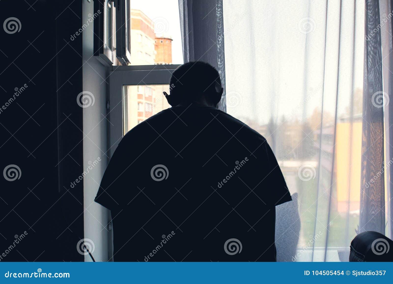 窗口的人,弯曲他的头下来在消沉,要自杀