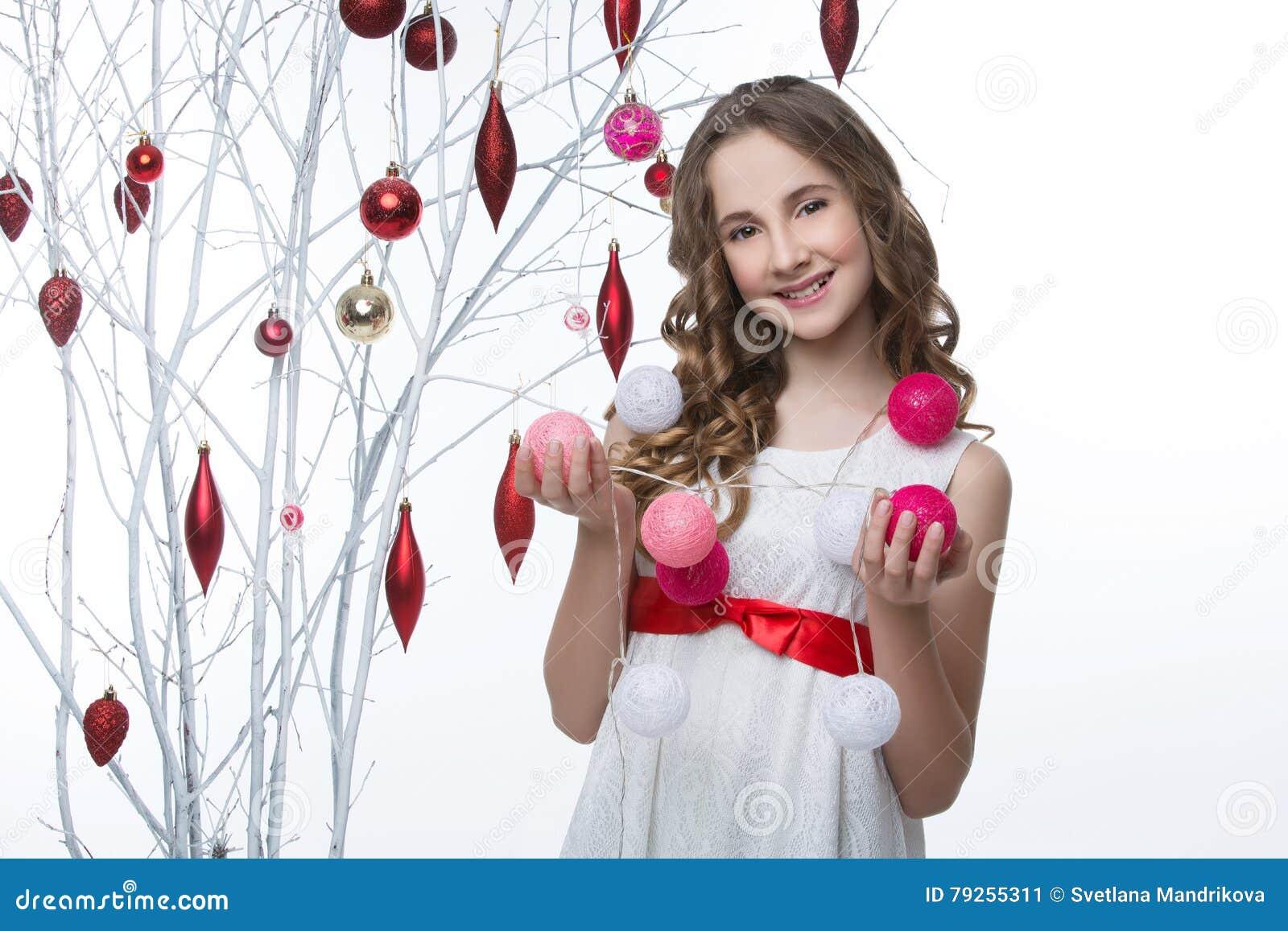 站立与圣诞节装饰的美丽的女孩近的树