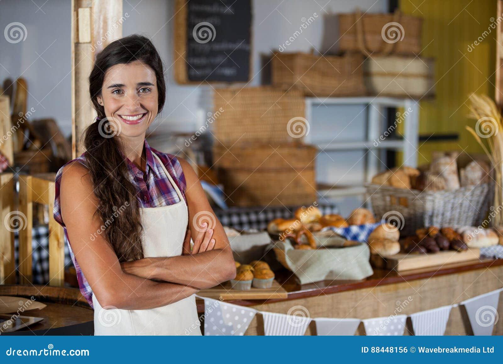 站立与胳膊的微笑的女职工画象横渡在面包店商店