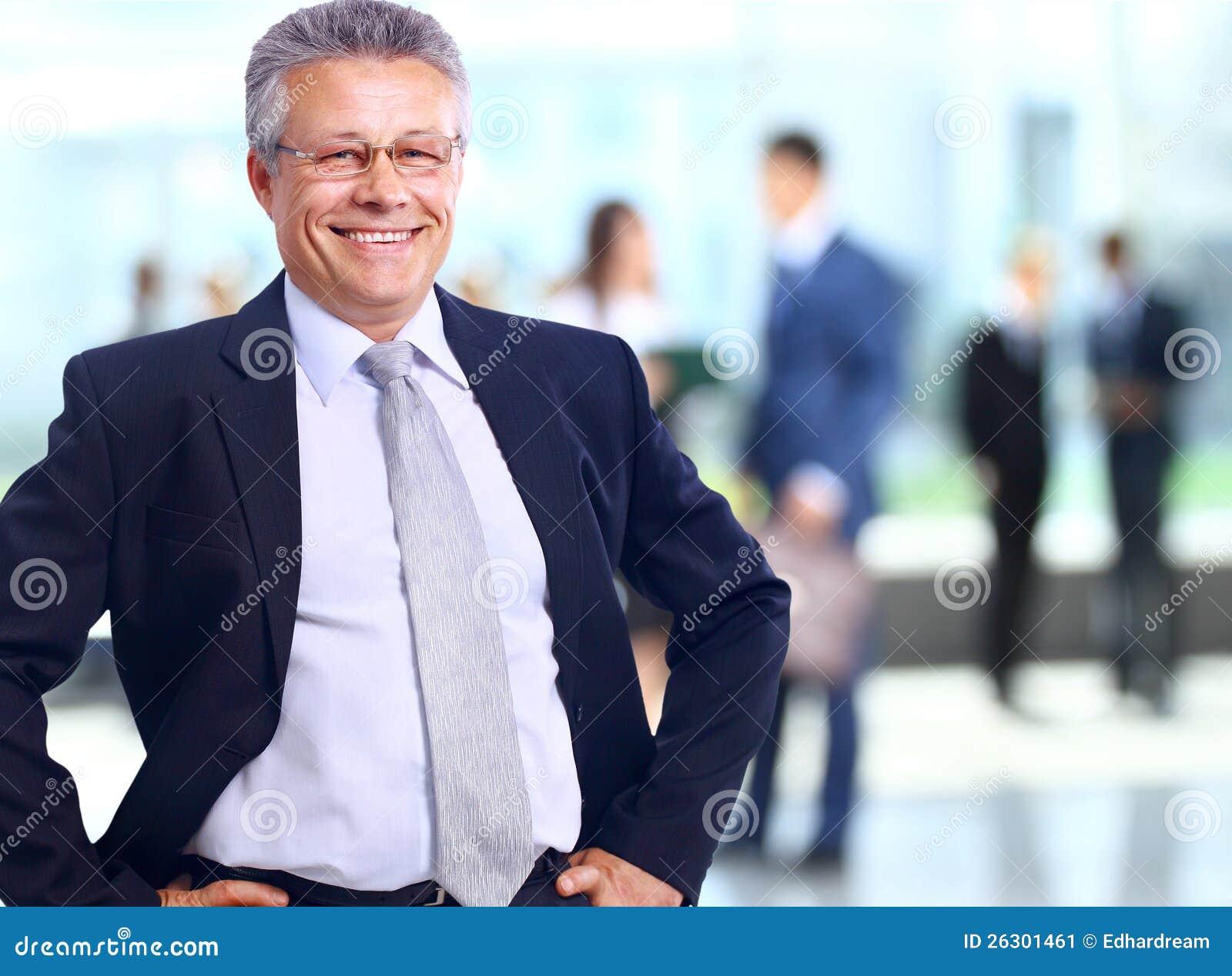 站立与他的职员的成功的商人在背景中在办公室