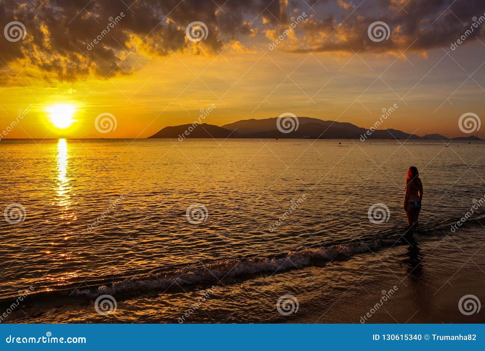 站立反对太阳的一名孤立妇女在芽庄市海滩