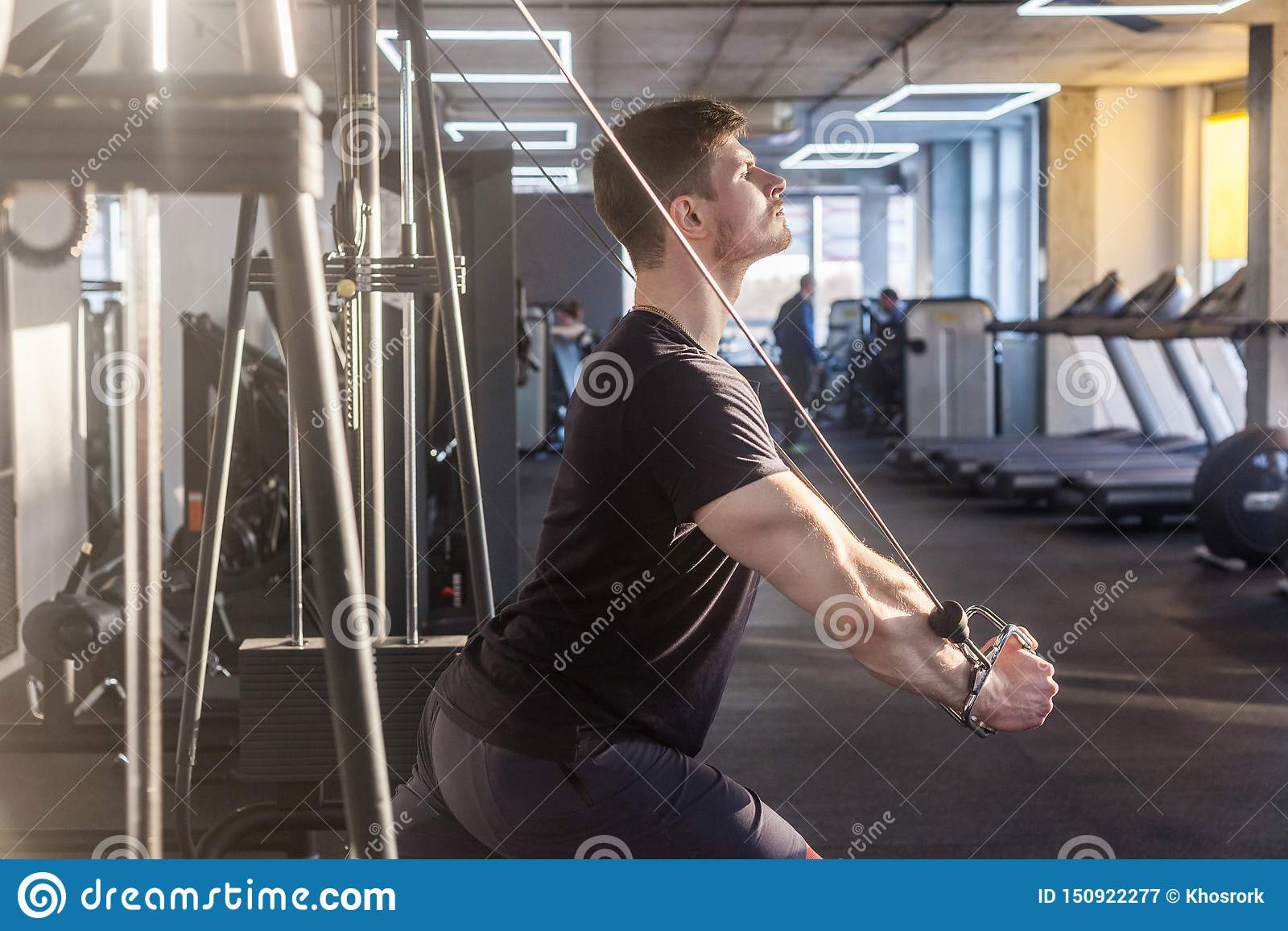 站立和做在单独健身房的年轻成人确信的crossfit人画象的侧视图关闭trx锻炼,训练