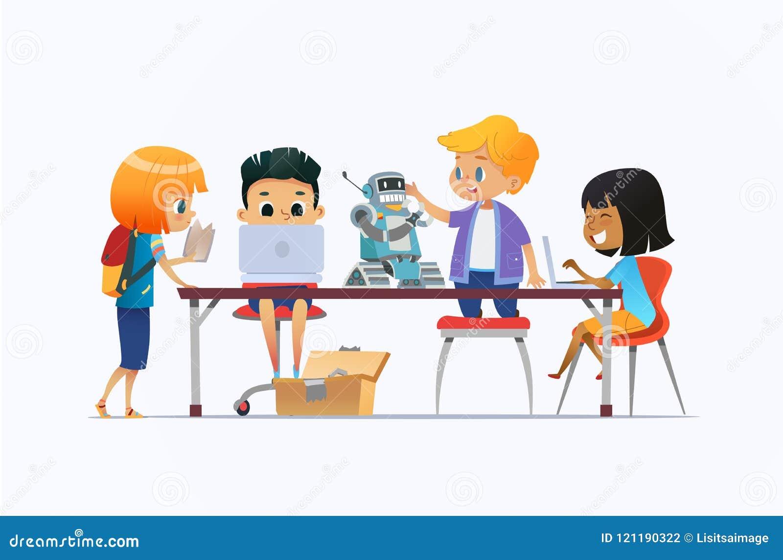 站立和坐在有膝上型计算机和机器人的书桌附近和研究编程的学校项目的男孩和女孩