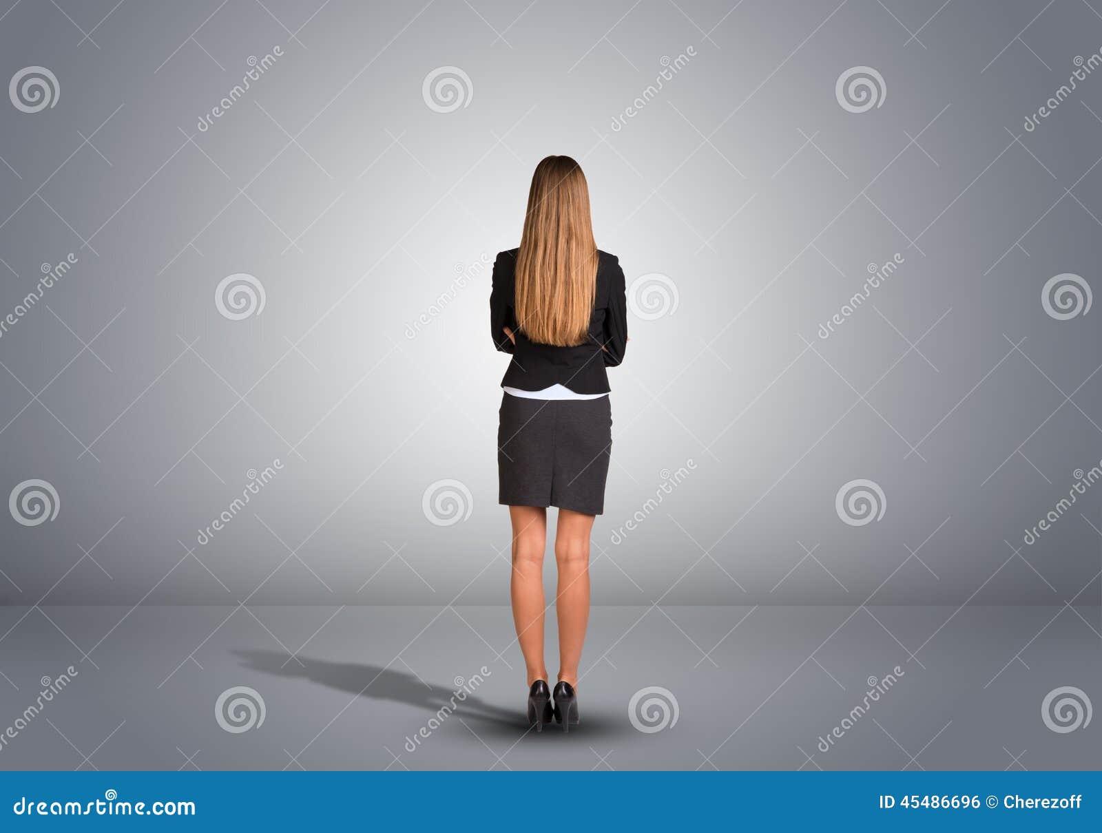 站立在一间空的灰色屋子的女实业家 后方