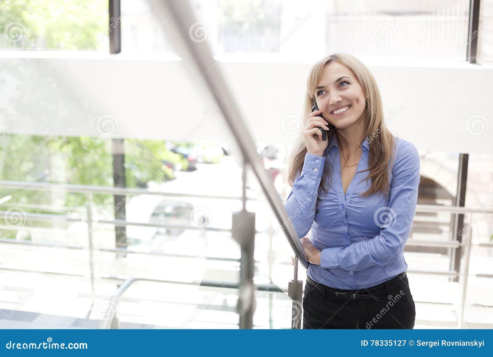 站立在与手机的一个现代大厦的女实业家
