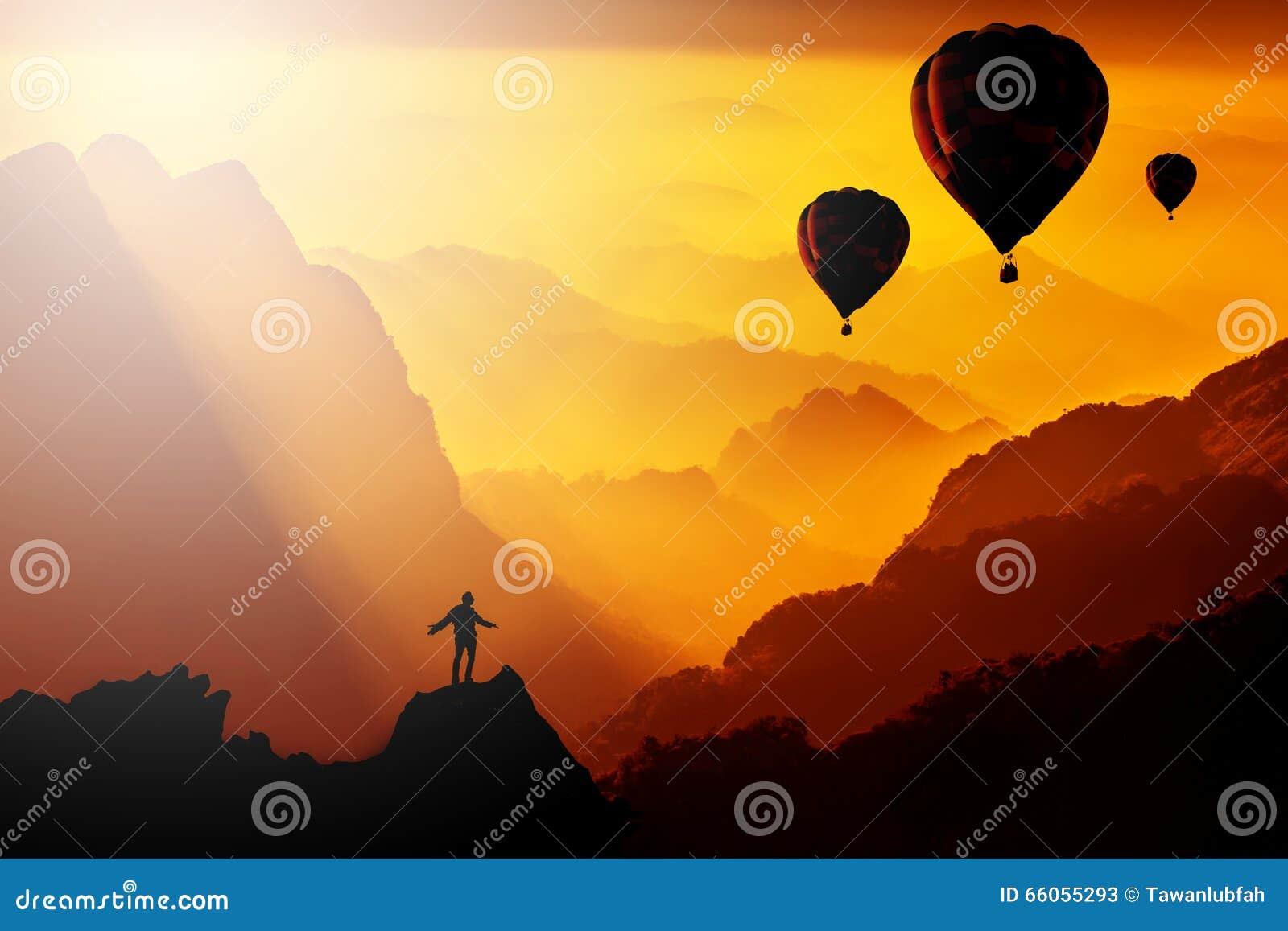 站立在与热气球fl的山的现出轮廓人