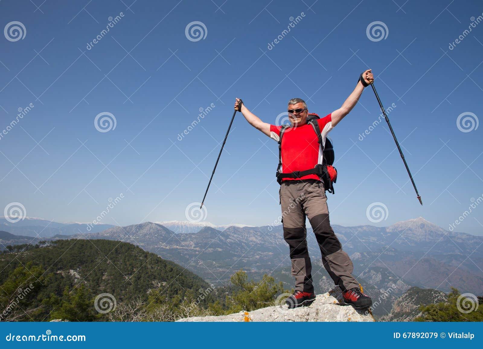 站立在与谷的山顶部的远足者在背景