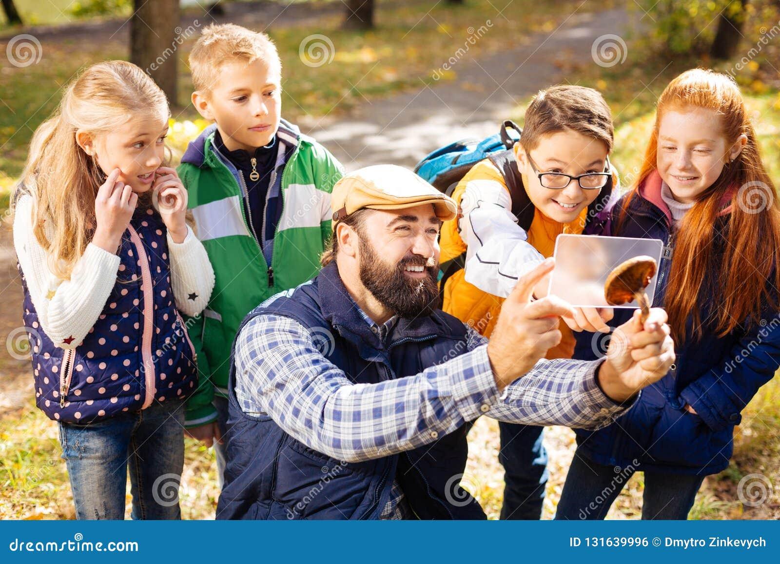 站立在他们的老师后的快乐的逗人喜爱的孩子