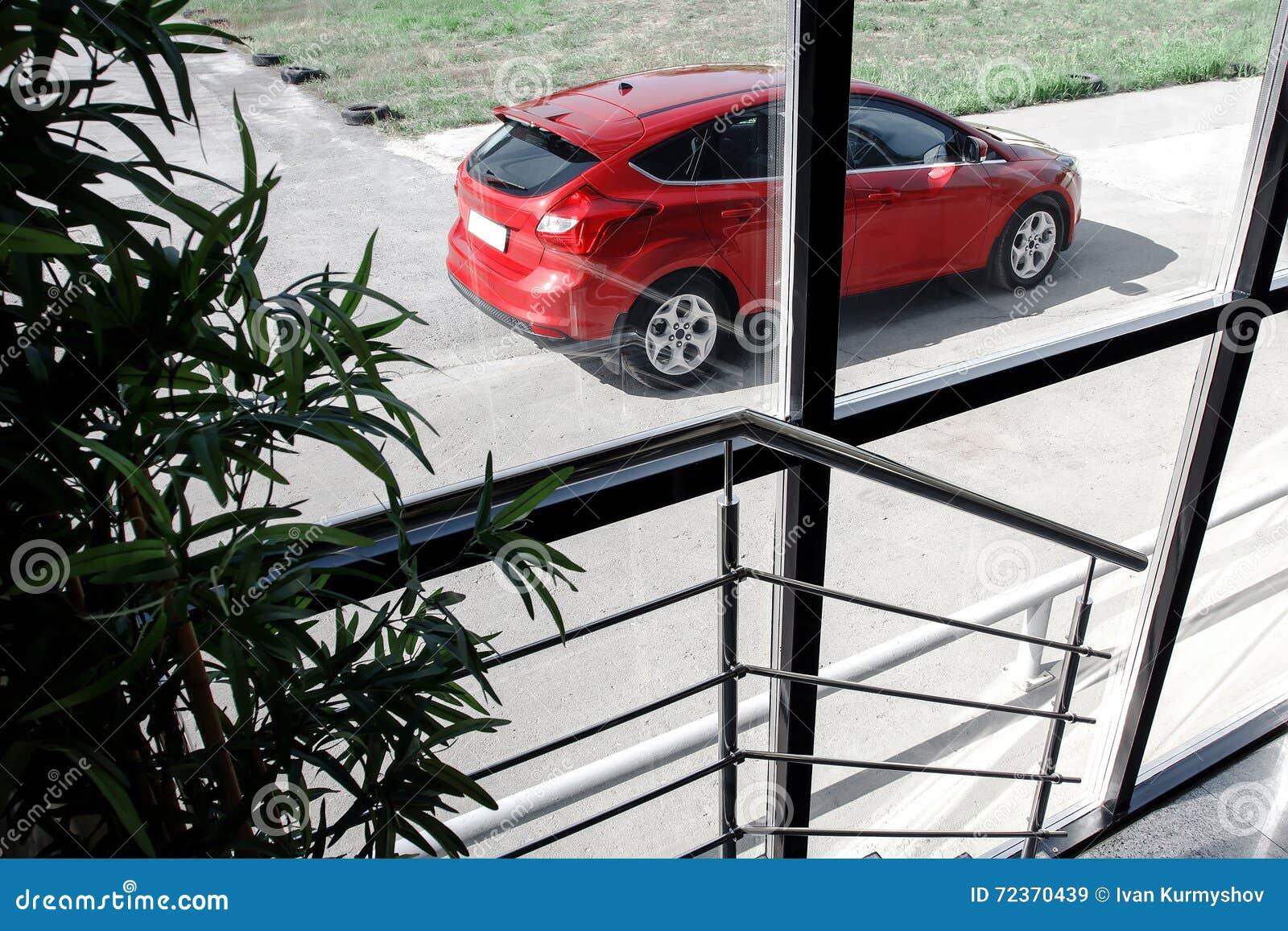 站立在修造附近的红色汽车