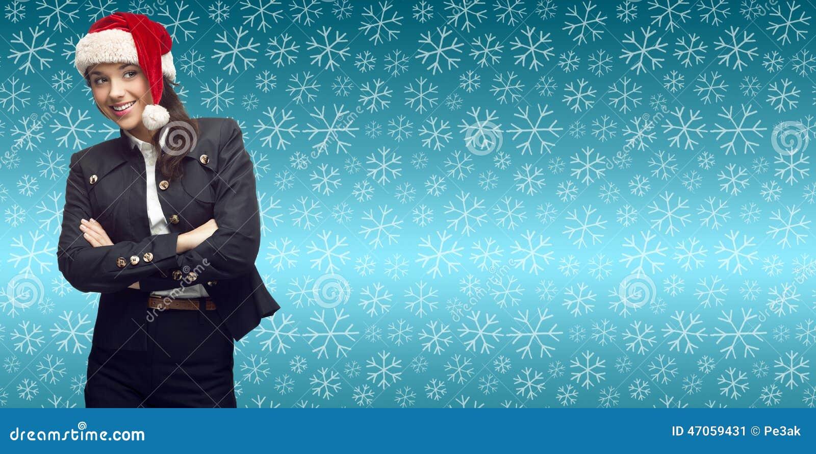 站立在冬天雪花背景的圣诞老人帽子的微笑的年轻女商人.图片