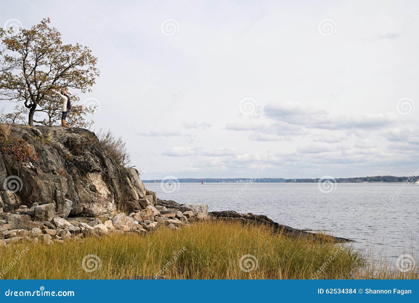 站立在岩石的妇女在湖附近