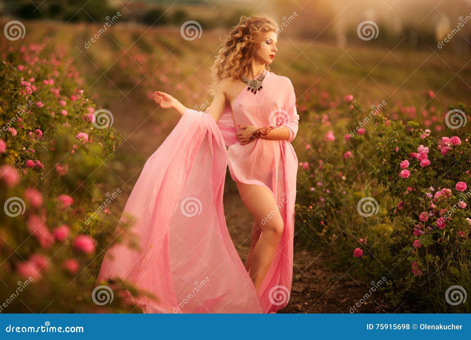 站立在庭院玫瑰的一件桃红色礼服的美丽的性感的女孩