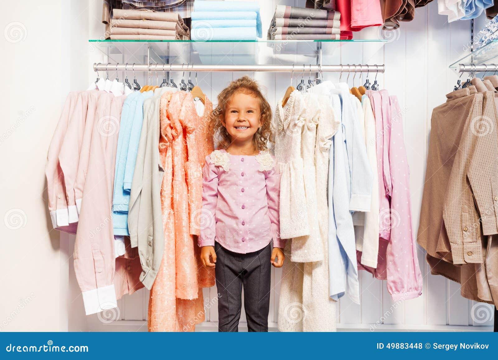 站立在挂衣架的衣裳之间的逗人喜爱的小女孩