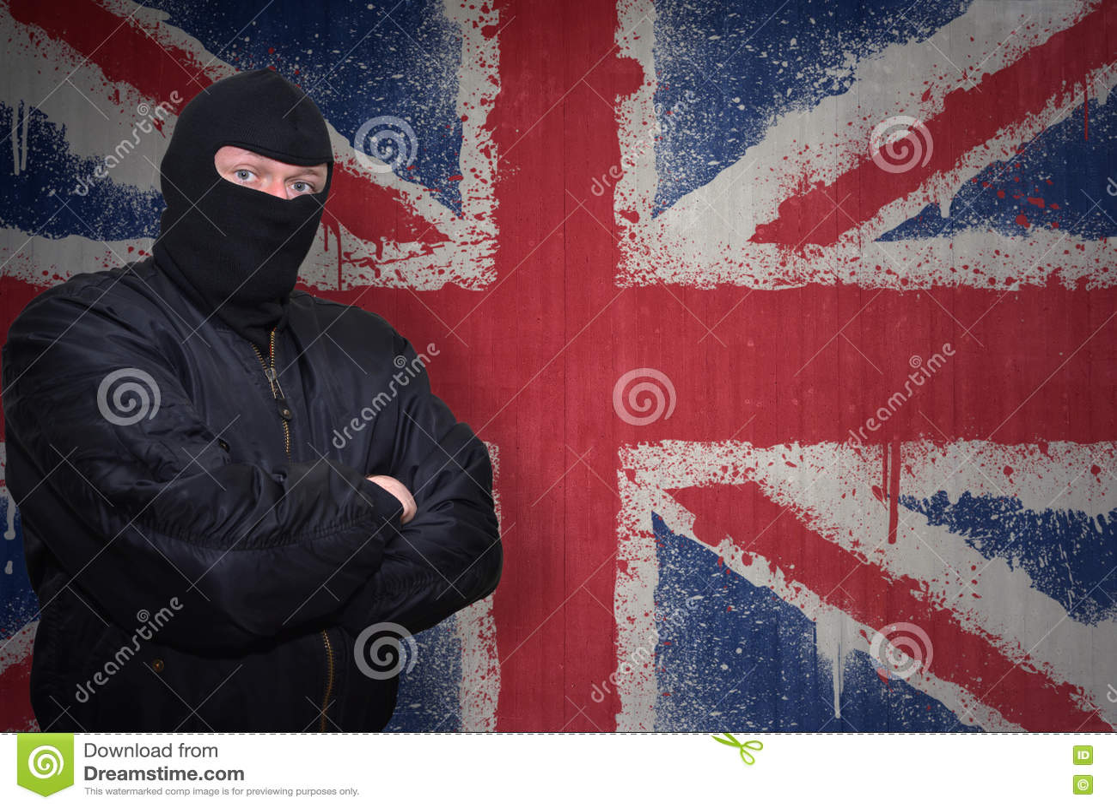 站立在有英国的被绘的国旗的墙壁附近的面具的人