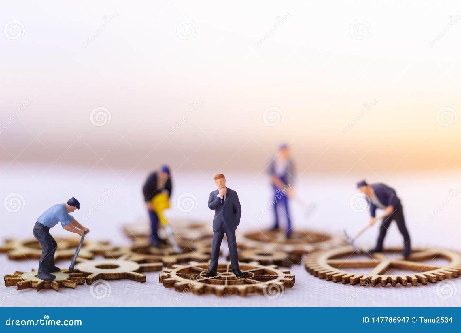 站立在木齿轮的商人和许多工作者