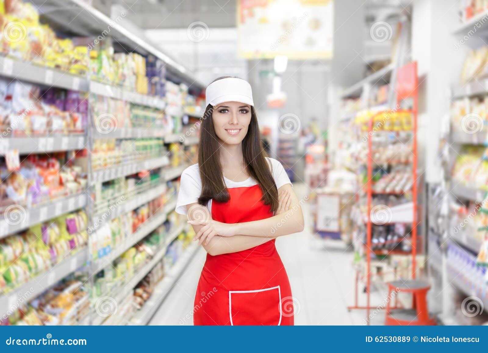 站立在架子中的微笑的超级市场雇员