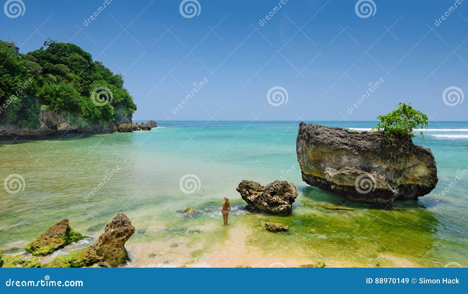 站立在水中的宽银幕观点的女孩在padang padang海滩在巴厘岛