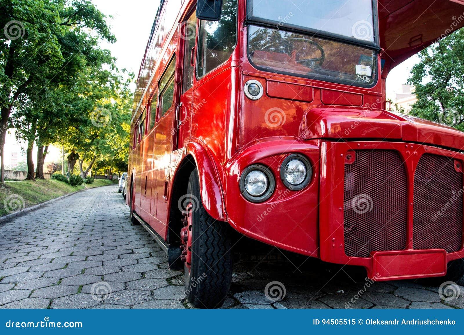 站立在江边的公园的红色两层英国公共汽车