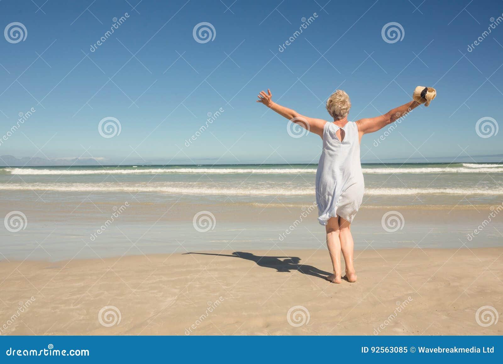 站立在沙子的妇女背面图反对清楚的天空