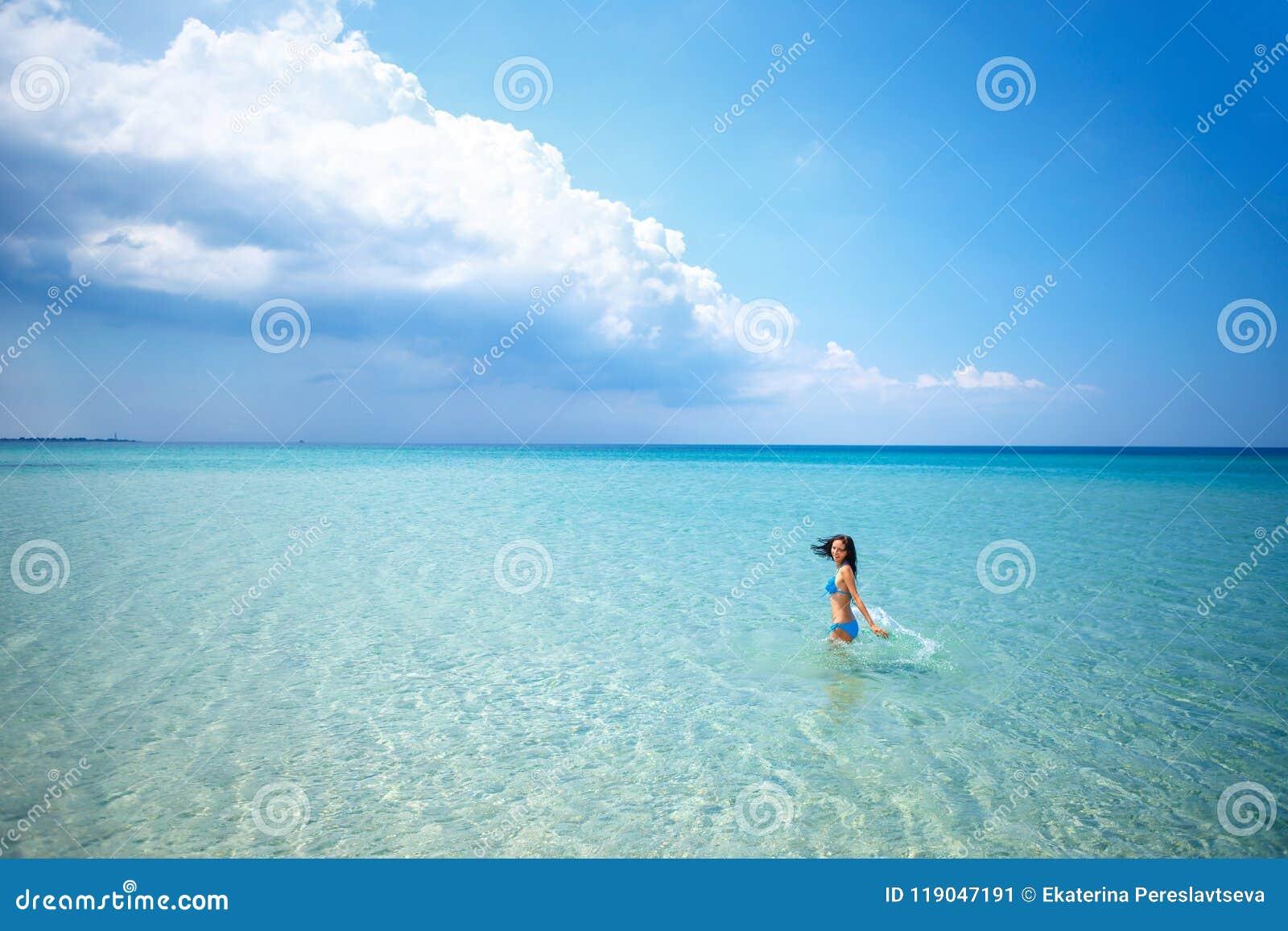 站立在泳装的美丽的愉快的妇女在蓝色海