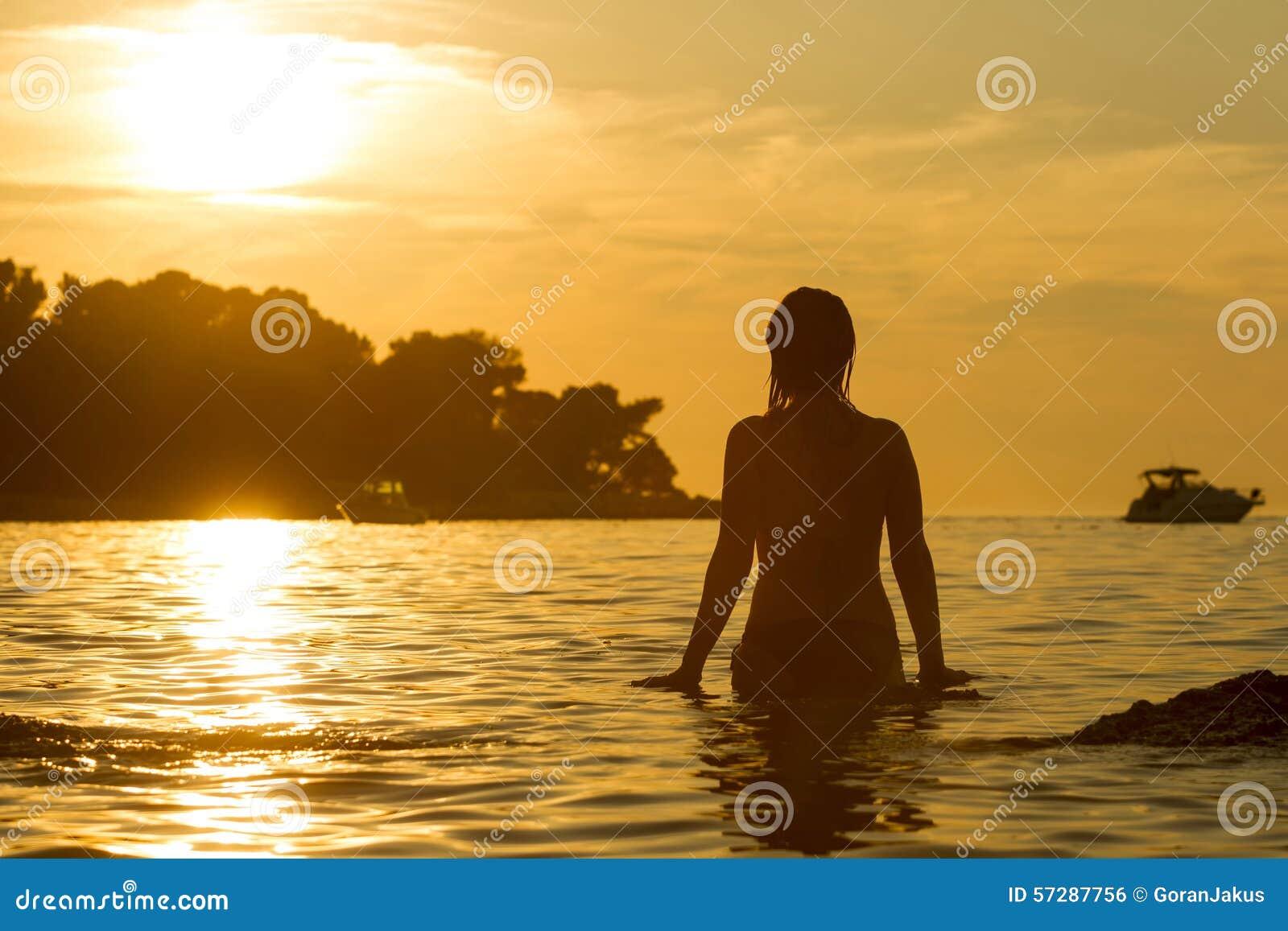 站立在浅的妇女在日落