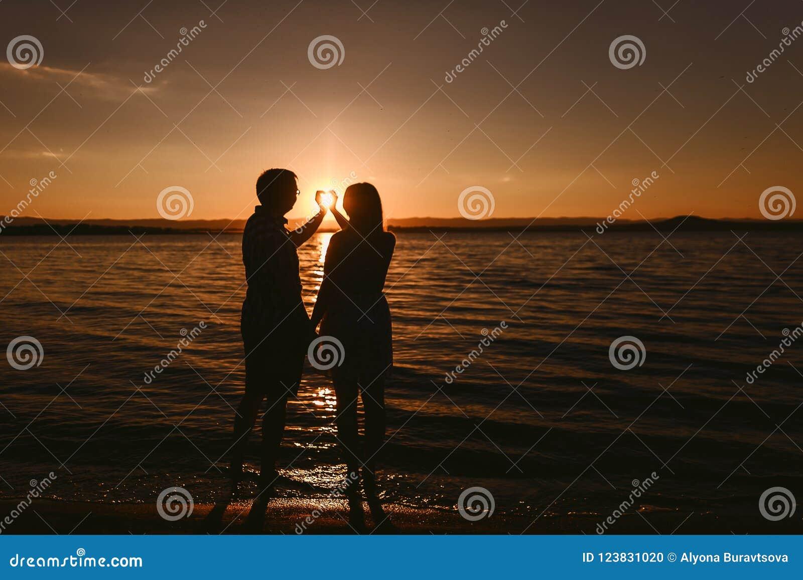 站立在海的男人和妇女在日落