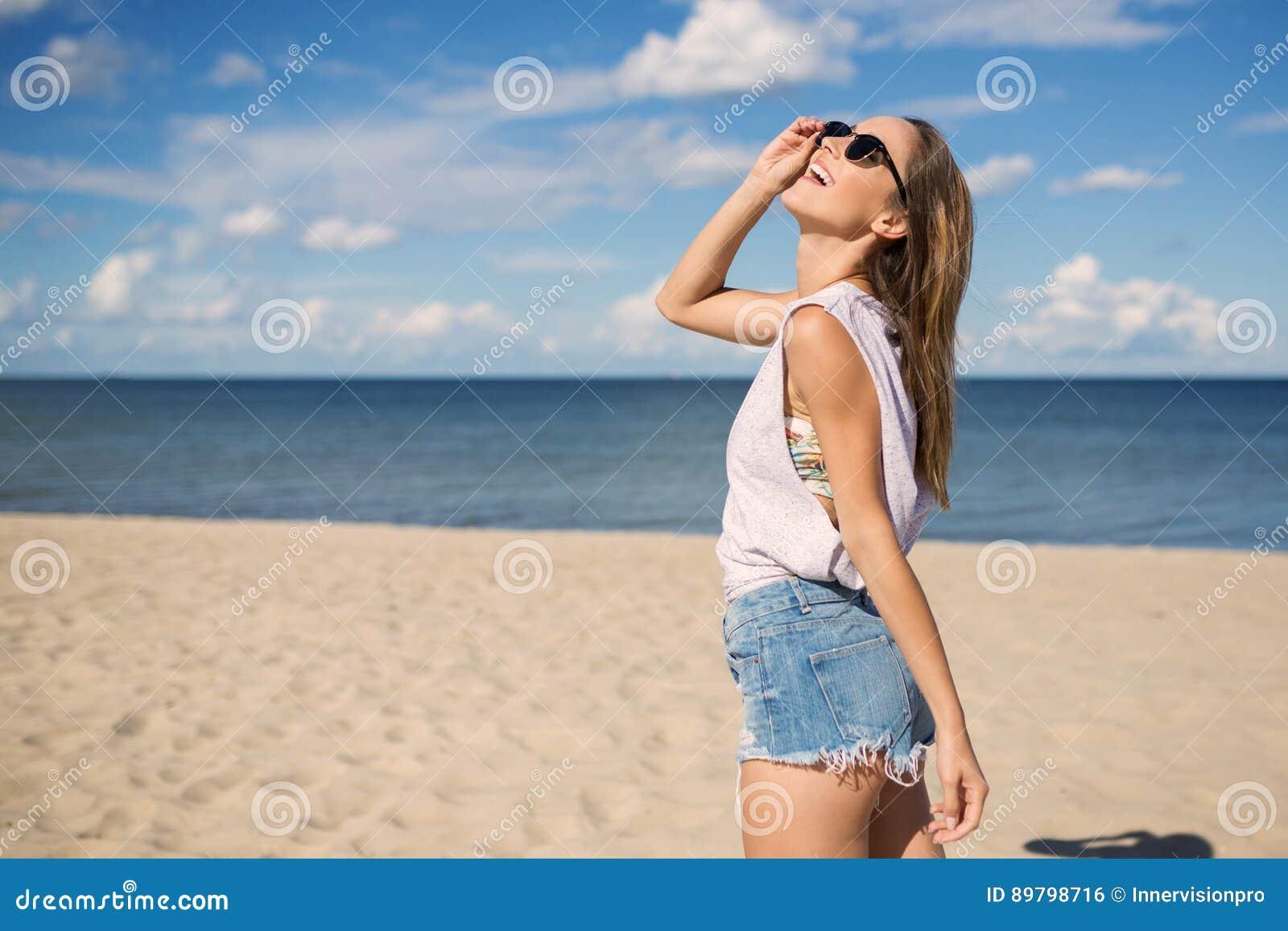 站立在海滩的愉快的少妇查寻
