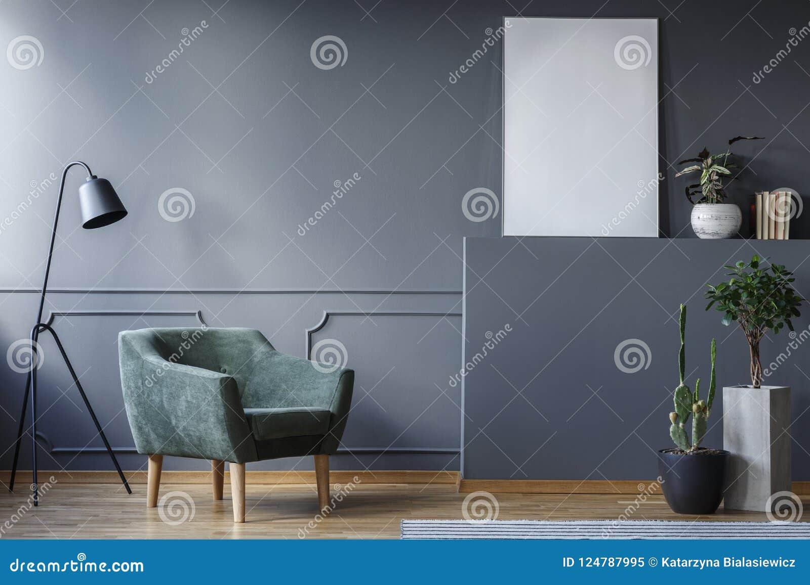 站立在灰色的一盏绿色扶手椅子和黑灯的真正的照片
