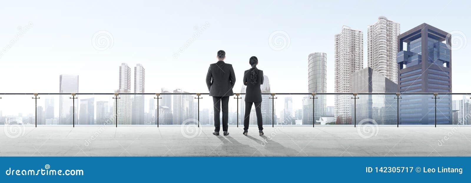 站立在现代大阳台和看看法的两个亚裔商人背面图
