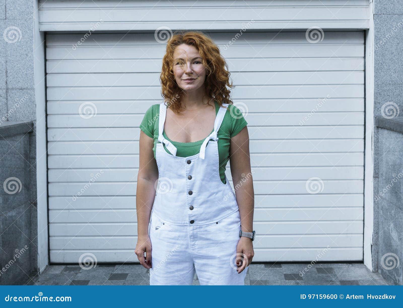 站立在白色总体的简单派白色样式的妇女 天,室外